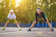 Son and mother are doing exercises on the stadium Royalty Free Stock Images