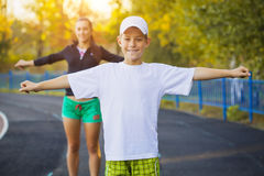 Son and mother are doing exercises on the stadium royalty free stock photo
