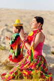 Son and mother dressed in Mexican clothes praying Stock Photos