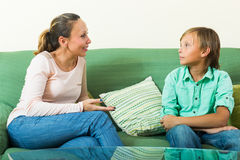 Son and mother having serious talking. On sofa in home royalty free stock photo