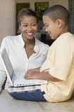 Son and mother in living room using laptop. Son sitting on counter in living room using laptop with mother, side view Royalty Free Stock Photo