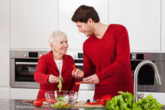 Son and mother making salad. Adult son and elderly mother making together healthy salad Royalty Free Stock Photography
