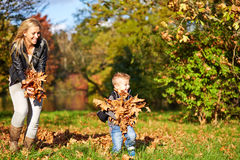 Son and mother playing together. In the autumn park royalty free stock photos