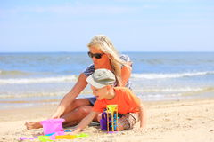 Son and mother playing toys on beach. Happy family child son and mother playing toys on beach sea background Royalty Free Stock Photo