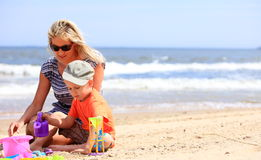 Son and mother playing toys on beach. Happy family child son and mother playing toys on beach sea background Stock Images