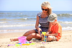 Son and mother playing toys on beach. Happy family child son and mother playing toys on beach sea background Royalty Free Stock Photos