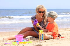 Son and mother playing toys on beach Royalty Free Stock Photo