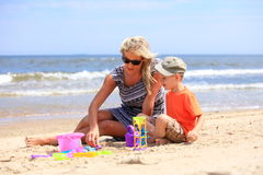Son and mother playing toys on beach. Happy family child son and mother playing toys on beach sea background Royalty Free Stock Images