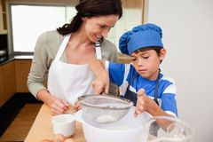 Son and mother preparing dough. Together Stock Image