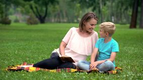 Son and mother reading interesting adventure book, sitting on blanket in park. Stock photo stock photo