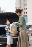 Son and mother with shopping bag in front of the car royalty free stock photography