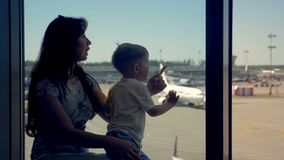 Son and mother sit in the airport looking to the airplanes. stock video footage