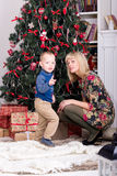 Son and mother. Are standing next to the Christmas tree Royalty Free Stock Photos