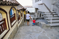 Son and mother walking on street of ?ncient city of Sozopol in Bulgaria Royalty Free Stock Images