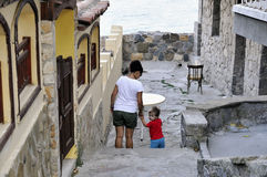 Son and mother walking on street of ?ncient city of Sozopol in Bulgaria Stock Photos