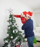 Son och fader Decorating Christmas Tree Arkivbilder
