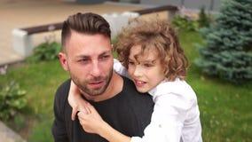 Son- och fadersamtal som sitter på en parkerabänk Pojken gestikulerar animatedly och skrattar En ung fader, ett lyckligt arkivfilmer