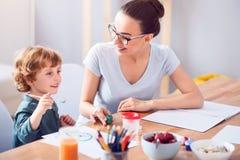 Son och moder som tillsammans målar arkivbilder