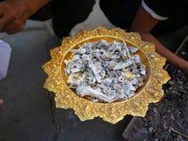 Son och släktingar av det avlidet, vem de samlade askaen i morgonen efter kremeringen på templet royaltyfria foton