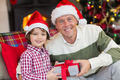 Son offering father a christmas gift on the couch. At home in the living room Royalty Free Stock Photography