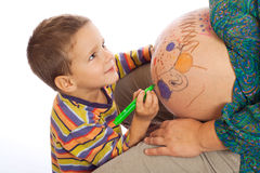 Son painting the belly of his pregnant mother Royalty Free Stock Images