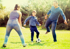 Son and parents playing football. In grass field Stock Images