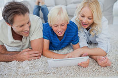 Son and parents using a tablet. Lying on a carpet Stock Photos
