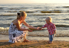 Son passing pebbles to his mother Royalty Free Stock Image