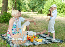 Son of photographs of parents mom and dad. Family on a picnic. Son of photographs of parents mom and dad Royalty Free Stock Image
