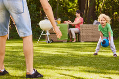 Son playing ball with father. Small son playing rugby ball with father in garden royalty free stock images