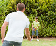 Son playing football with his father. In the garden Stock Photography