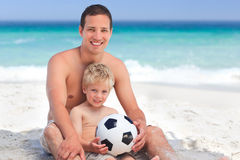 Son playing football with his father. At the beach Royalty Free Stock Images