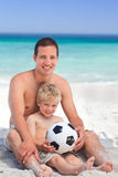 Son playing football with his father. On the beach Stock Photography