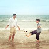 Son playing with a football  while his father watche. Son playing with a football on the beach while his father watches Royalty Free Stock Photo
