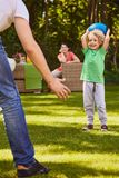 Son playing with his father. Little son playing rugby in the garden with his father royalty free stock images