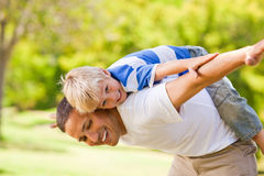 Son playing with his father outside. Son playing with his father in the park Stock Images
