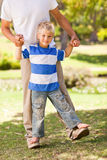 Son playing with his father in the park Royalty Free Stock Images