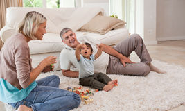 Son playing with his parents Stock Images
