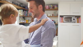 Son Playing In Kitchen Greeting Father Returning From Trip