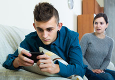 Son playing with phone, mother trying to talk Royalty Free Stock Photos