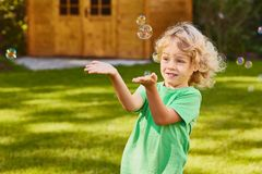 Son playing with soap bubbles. Little son playing with soap bubbles in the garden Royalty Free Stock Photography