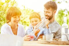 Son pours water into glass for parents. Son pours water into glass in the garden in summer Stock Photo