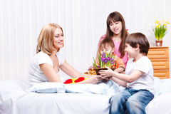 Son presenting flowers. To mother Stock Photography