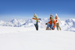 Son pulling father on sled through snow as mother and daughter push Stock Photo
