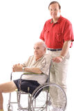 Son pushing his father in a wheelchair. Isolated on a white background Royalty Free Stock Photo