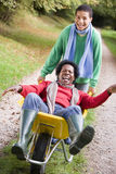 Son pushing mother in wheelbarrow. Son pushing laughing mother in wheelbarrow Royalty Free Stock Images