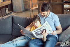 Son reading newspaper to father at home. Focused son reading newspaper to father at home royalty free stock photos