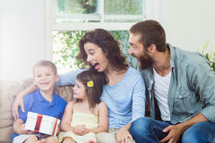 Son receiving surprise a gift from her parents. In living room Stock Image