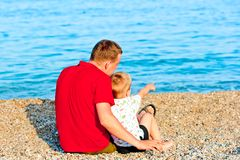 Son reveals that his father is in the sea, they are sitting. On the beach royalty free stock photo