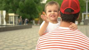 Son rushes into father`s arms at park.